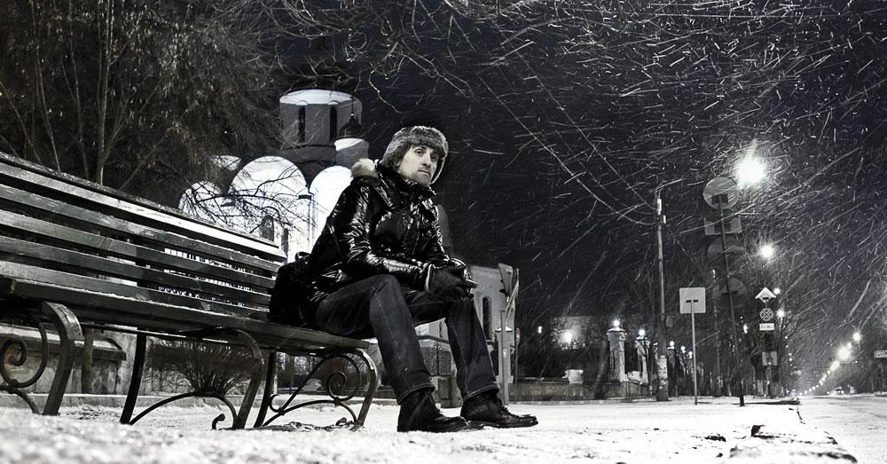 Ночной зимний Тирасполь и человек, сидящий на скамейке