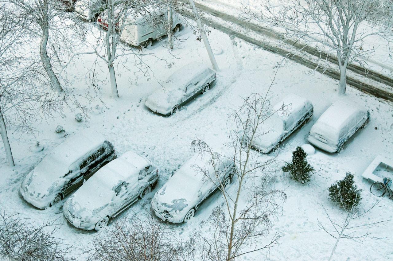Автомобили зимой во дворе на газоне